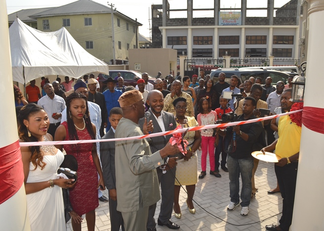 Prof. Tony Anwukah cutting the ribbon and observed by Rev. Ojirika, D'ness (Mrs.) Ojirika, Dr. Bello and a host of invitee's