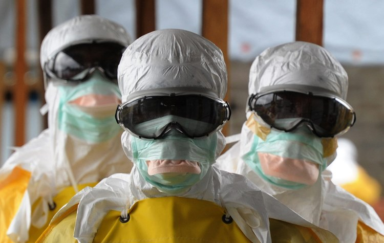 Health care workers, wearing protective suits. (Getty Images)