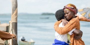 Lupita Nyong'o as Harriet in Queen of Katwe hugs 10-year-old Madina Nalwanga (Phiona Mutesi)