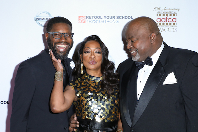 Shawn Edwards (L), co-founder of AAFCA and Gil Robertson (R) co-founder and President of AAFCA flank Tichina Arnold of The Neighborhood who served as the host of the 10th Annual AAFCA Awards